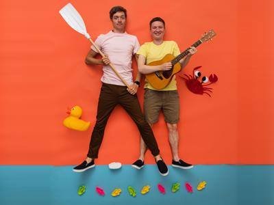 Mole and Gecko: two people are in front of an orange background, one person wearing a light pink shirt holding an oar the other wearing yellow and holding a guitar.