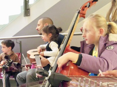 a group of children and parents, holding string instruments and watching something intently