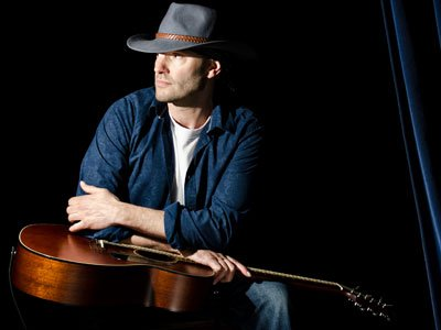 A man with a cowboy hat sits on a dark stage, himself and the guitar gleaming in a spotlight