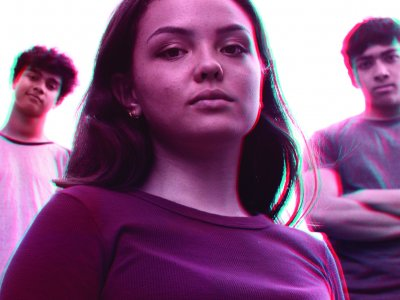 A girl stands in the foreground with two boys behind her. Theyre looking at the camera not smiling. There's a pink and crackly filter over the image.