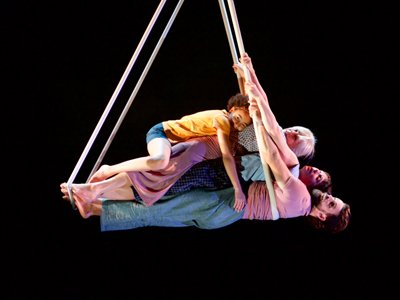 Four people lie on top of each other, suspended off the ground. They are held up by white poles on a black background.