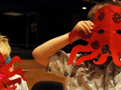 Child holding up a red glittery octopus mask