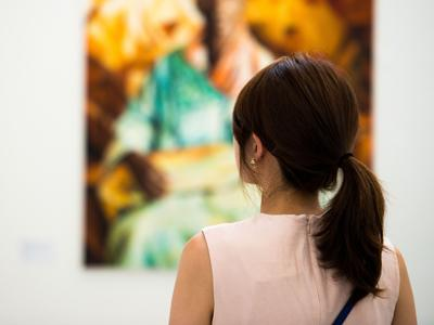 the neck and back of a woman in a brightly-lit gallery space. In the background a blurry image is visible