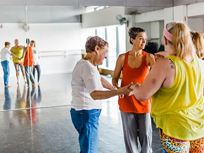 A group of dancers in colourful sportwear gather in a rehearsal room