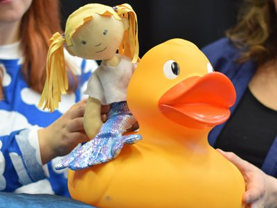 A small puppet of a girl is riding on the back of a rubber duck.