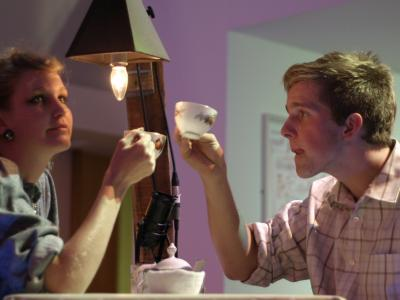A performance image of a couple sat at a table drinking tea