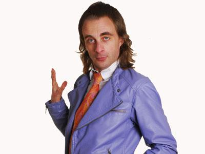 Paul Foot striking a pose in a purple leather jacket, white shirt and orange-patterned tie