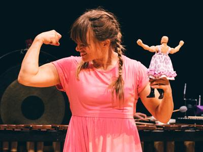 Plink and Boo: a performer in a pink dress admires her own biceps, while holding up an adventure figure in a dress in the other hand