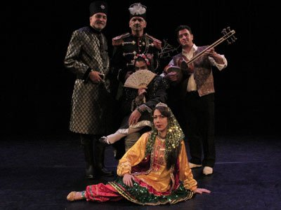 Three men in vaguely military costumes stand next to each other, one holds a guitar. In front of them sit two women. One is dressed in black and covers her face, the other wears a yellow Persian dancing costume and sits confidently.
