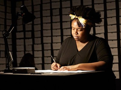 Race Cards: Selina Thompson sits in a darkened room on a desk lit by a desk lamp. She is writing on cards.