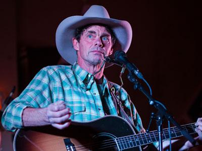 Rich Hall wearing a cowboy hat and strumming a guitar looking wearily into the distance