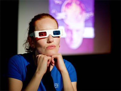 Rosy Carrick on stage, wearing blue and red plastic 3D glasses. She rests her head on her hands and looks into the camera