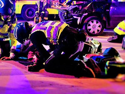A street lit by street lamps and crowded with firefighters. Two medics kneel over an injured motorist.