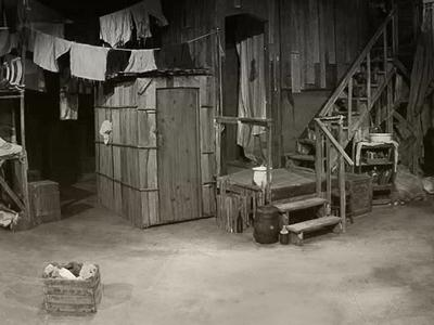 black and white image of a basement room with clothes hanging on a line and stools around the room