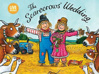 The Scarecrows' Wedding: a male and a female scarecrow stand on a field and smile at each other. They are surrounded by cows.