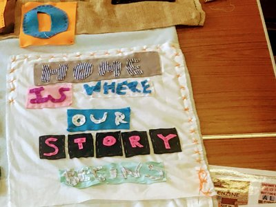Hashtag SelfCare: Cut-out fabric letters on a white sheet, spelling 'Home is where our story is'