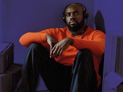 An actor sits on the floor wearing headphones