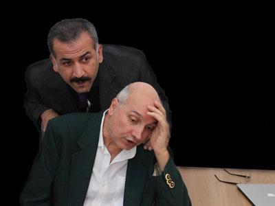 A photo of two men standing over a desk in a play by Seven Theatre.
