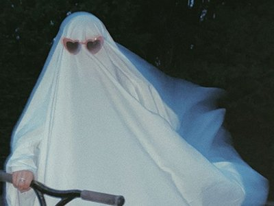 A ghost wears pink heart shaped sunglasses while riding a bmx