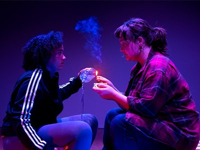 Two performers sit opposite eachother, one holds a water bottle with water pouring out and the other lights a match