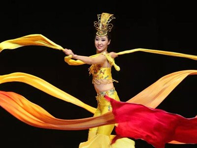 Silk Road Dance Festival: a Chinese dancer in tradional clothing, spinning surrounded by flowing yellow and red silk