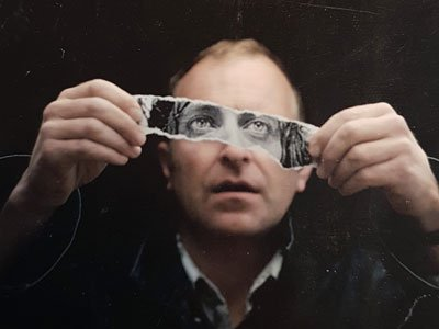 Simon Evans: an face of a man holding up a strip of paper covering his eyes, showing another man's eyes
