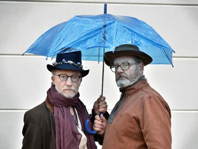 Sockful of Custard: two men in coats and scarfs standing under a blue see-through umbrella