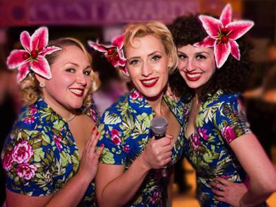 The Spitfire Sisters singing trio posing with pink lilies in their hair