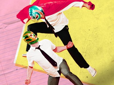 Square Go: a man in a green wrestling mask and a red cape jumps on a man in a blue mask and white shirt. The background is composed of pink lined paper and yellow grubby floor material