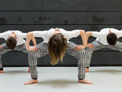 three people dance in front of a black wall. They are bent over, you can only see the tops of their heads, their shoulders, and their turned out legs in black-and-white patterned trousers