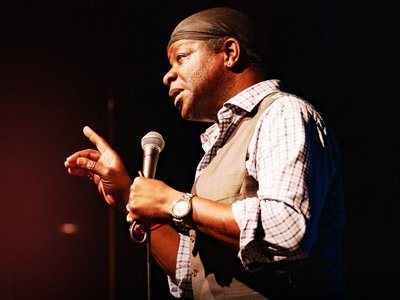 Stephen K Amos, photographed in glowing golden light, talks into a microphone and raises his finger as if making a point