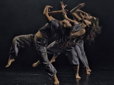 Still I Rise: three women in blue loose clothes dance with their hands swirling above them and their backs arched back