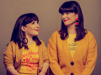 Lisa Hammond and Rachael Spence, dressed in yellow, smiling at each other