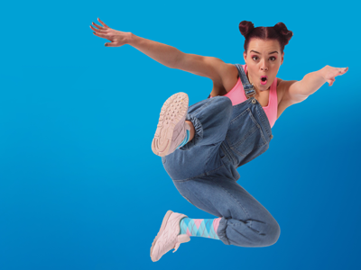 a girl in a pink t-shirt and blue jeans dugarees jumps in the air, one leg kicking out in front of her, her arms spread. The background is electric blue.