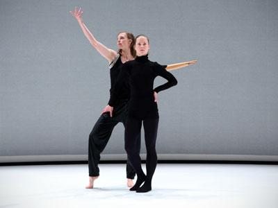Two Women Stand Resolute on a Bare Stage