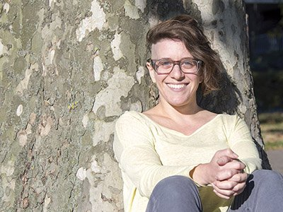 Tamara Micner, a white woman with glasses and dark hair shaved short on one side, is pictured outside. She is leaning against a tree and smiling at the camera.