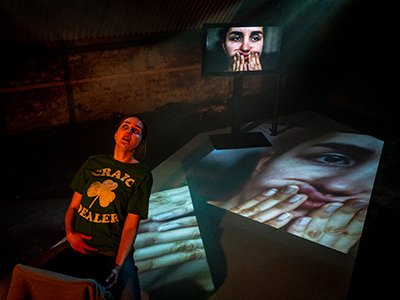 A person stands looking distressed next to two projections of themselves, where they squish their face with their hands
