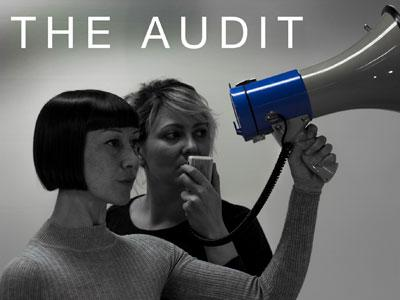 The Audit - Two performers stand defiant, one holding a loud speaker