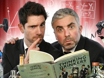 The Thinking Drinkers sitting behind a table reading a book