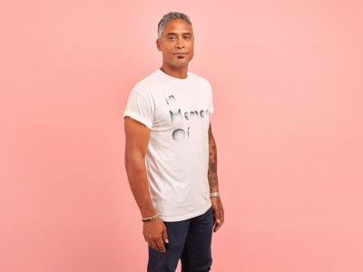 A man wearing a white t-shirt which reads 'In memory of' stands in front of a pink background