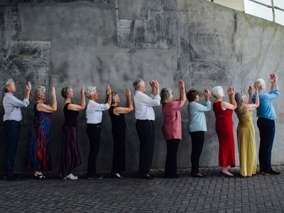 Three Score Dance Company: eleven dancers aged over 60 stand in a line, holding their hands in front of their faces