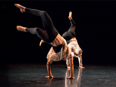 Moving Words: two dancers in black leggins and loose white shirts perform a stunt on their hands
