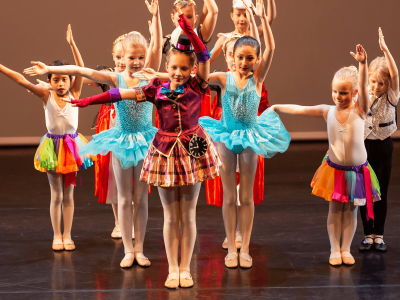 A group of children dancing on stage in regal costumes