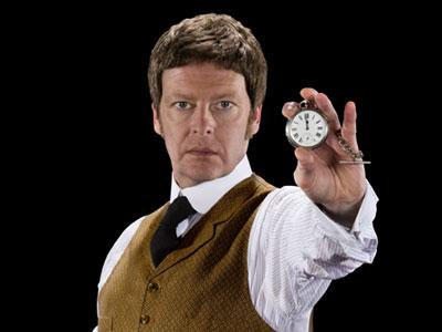 A man in Victorian clothing holding a pocket watch towards the viewer