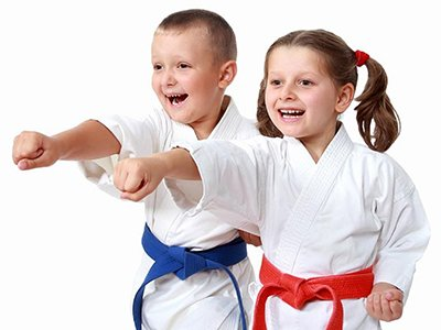Two children dressed in karate gear, doing a karate punch. Both are smiling.