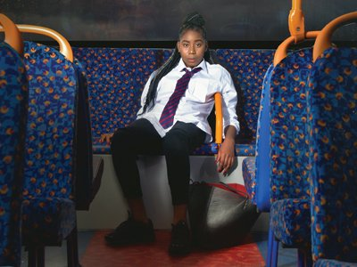 Who Cares: a girl in a school uniform sits in the back of an empty bus's upper deck