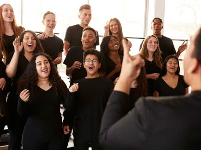 A group of teenagers and young adults stands in rows, singing with smiling faces