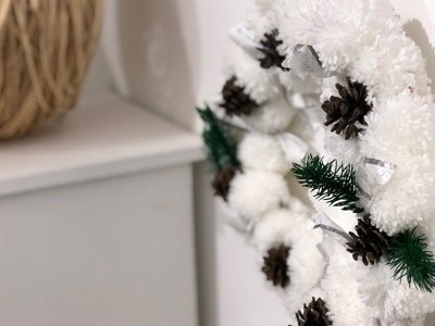 a wreath made from white pipe cleaners ornamented with pine cones