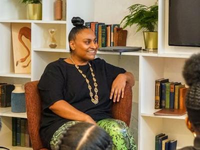 a black woman leading a workshop smiling