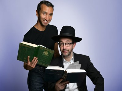 Ashley Blaker and Imran Yusuf: one man, dressed in traditional Jewish clothing, sitting and holding the Torah; behind him another man stands holding the Quran